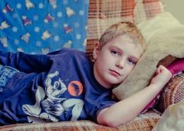 Niño enfermo tumbado en un sofá