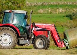 Un tractor en el campo enrollando heno