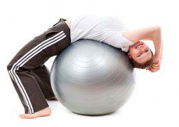 una mujer practica ejercicio físico sobre un balón de fitness