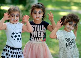 Tres niñas pequeñas juegan con las caras pintadas