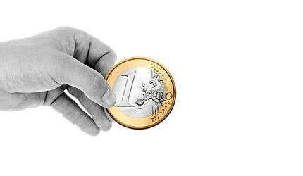 Una mano sujeta una moneda de euro