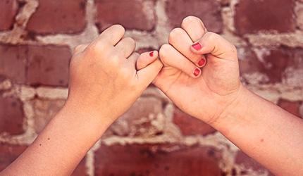 Dos manos con dedos entrelazados