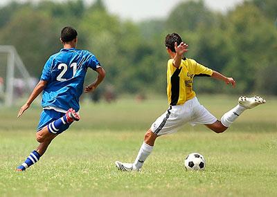 Dos jugadores de fútbol disputan un balón