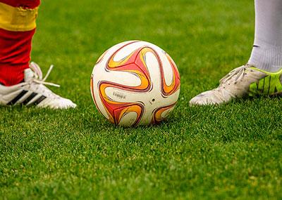 Dos piernas de futbolistas con un balón enmedio