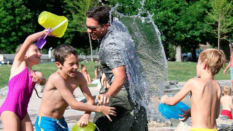 Un padre juega con sus hijos lanzandose agua