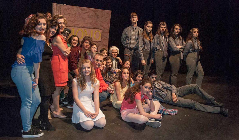 El elenco de actores sobre un escenario negro