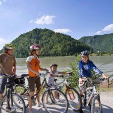 Una familia con sus bicicletas junto a un lago