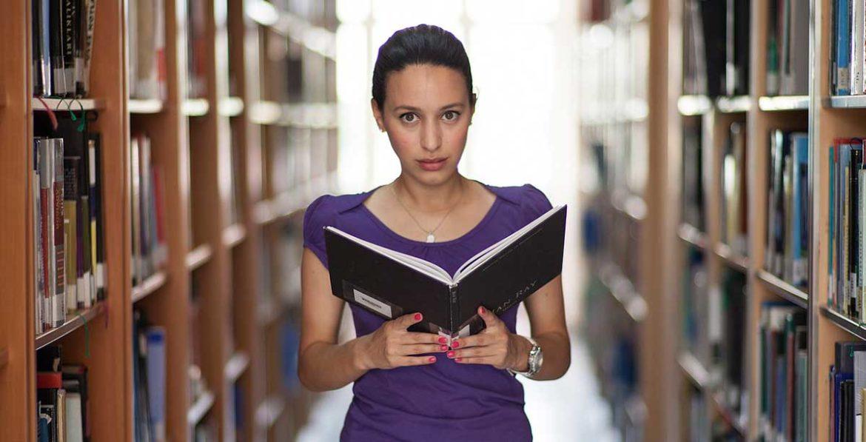 Una mujer sujeta un libro entre estanterías