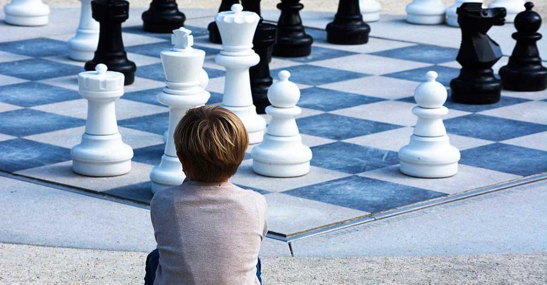 Un niño de epaldas contwmpla un tablero gigante de ajedrez