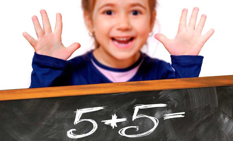 Una niña sonríe detrás de una pizarra