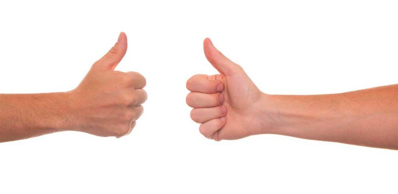 Dos manos enfrentadas con los pulgares hacia arriba
