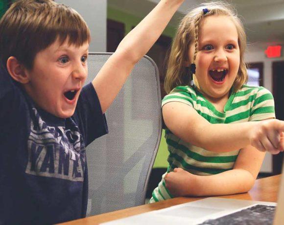 Dos niños juegan con un portátil