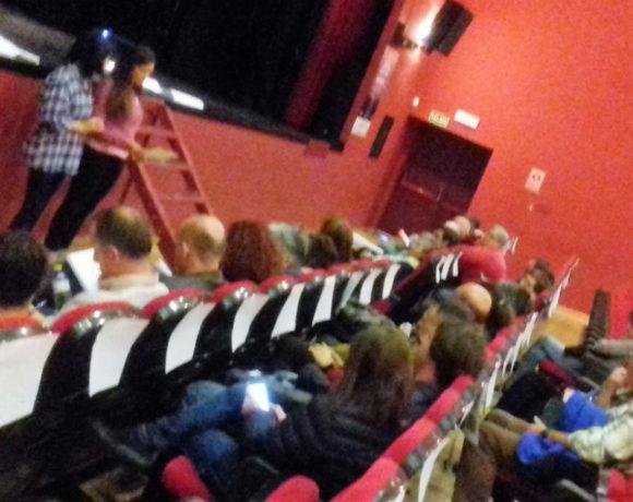 Reunión de gente hablando en un teatro