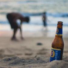 Una botella de cerveza en la playa y unos niños al fondo