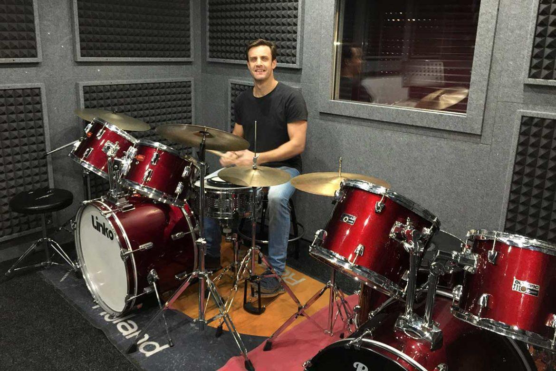 Una sala de música insonorizada con un músico tocando la batería