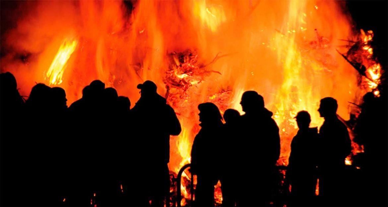 Siluetas de gente delante de una gran hoguera
