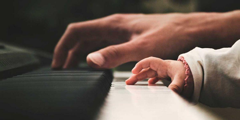 Una mano de adulto y otra de bebé tocan un piano