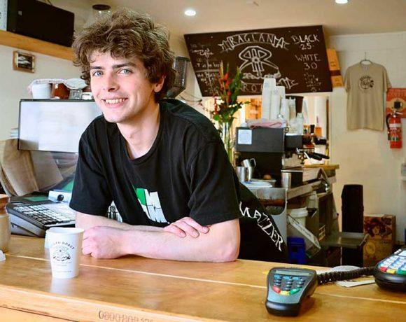 Un camarero joven sonríe detrás de una barra