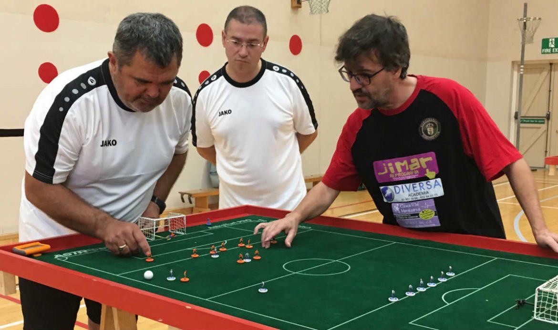 Treas hombres jugando al fútbol de mesa