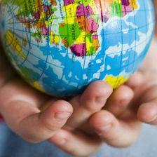 Unas manos de niño con una bola del mundo