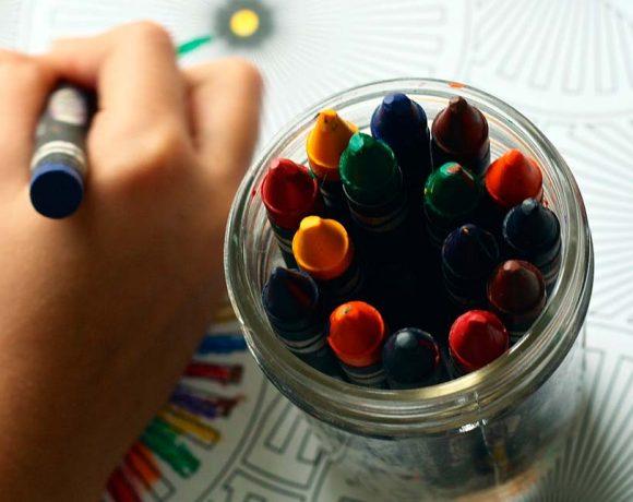 Ceras de colores y una mano de niño