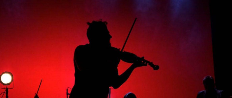 Contorno de un violinista con fondo rojo