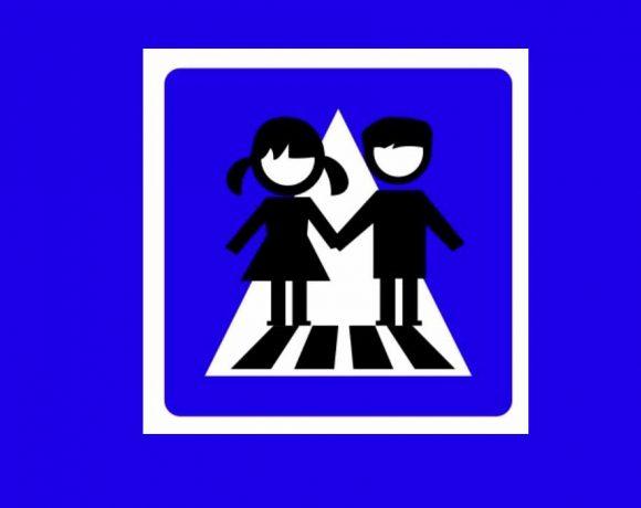 iconos de un niño y una niña sobre paso de cebra