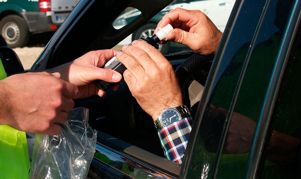 Manos de un conductor recibiendo alcoholímetro