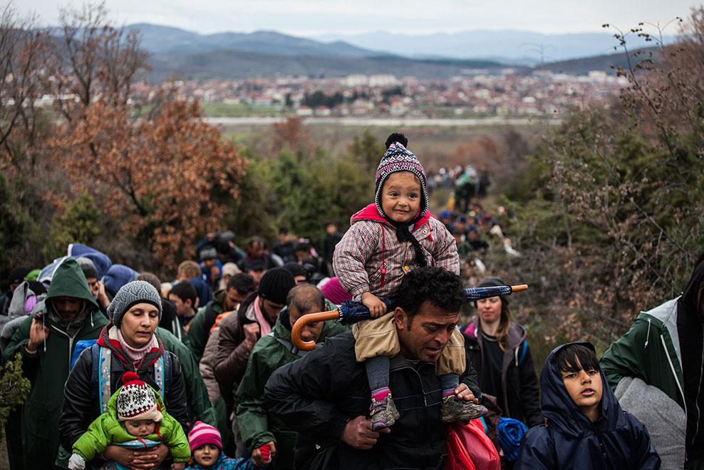 Un hombre porta a su hija a hombros en un grupo de refugiados