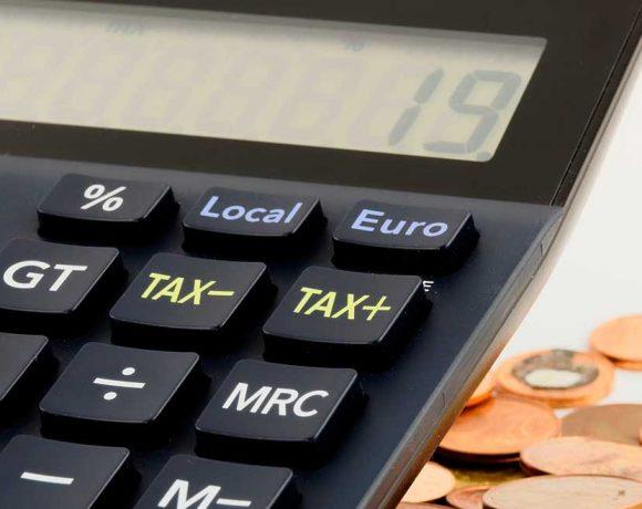 Una calculadora y monedas de fondo