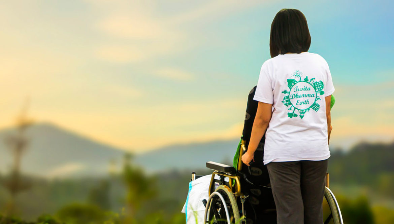 Una mujer empuja una silla de ruedas