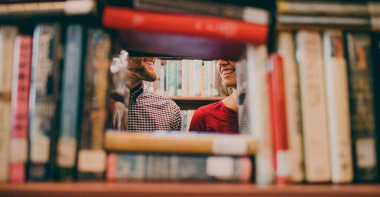 Un hombre y una mujer detrás de un estantería de libros
