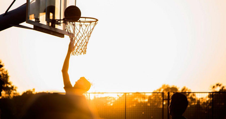 Dos jugadores de baloncesto en una canasta al aire libre