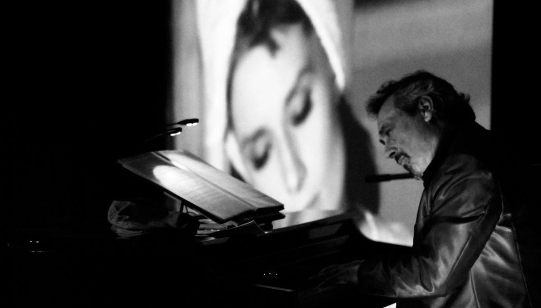 Un pianista con fondo de una proyección de una película