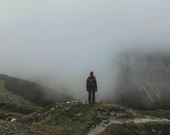 Un hombre asomado a un valle con niebla