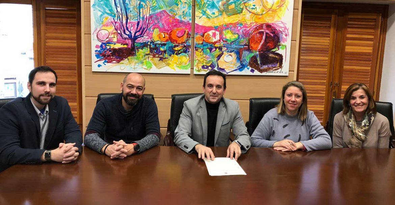 Cinco personas sentadas en una mesa tras la firma de un acuerdo