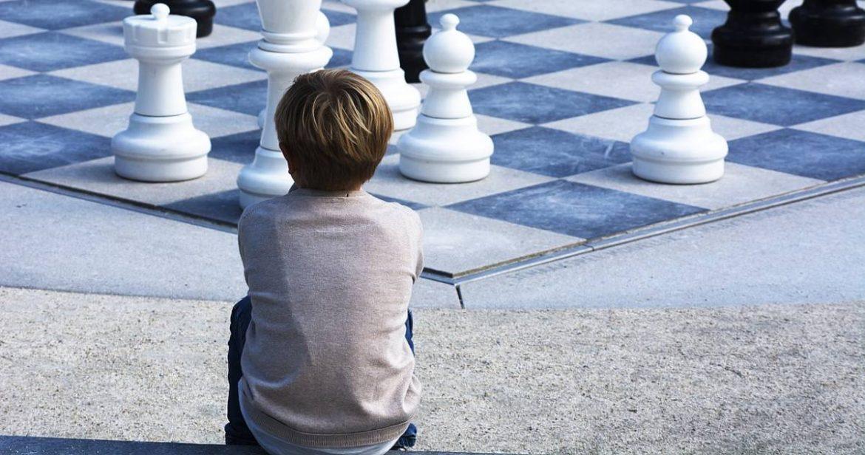 Un niño sentado de espaldas mirando un tablero gigante de ajedrez