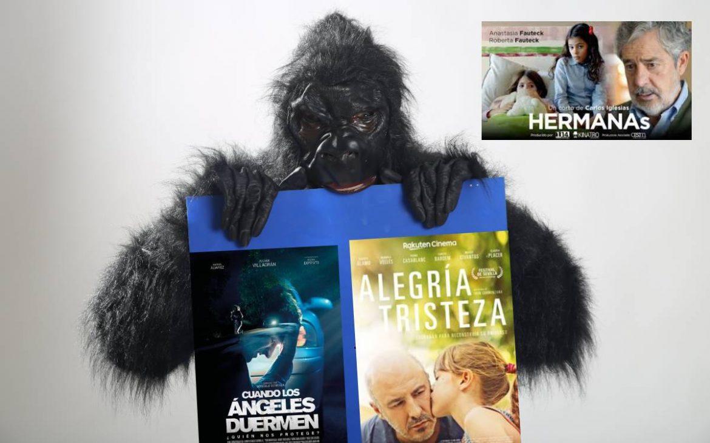 Una persona disfrazada de gorila con los carteles de dos películas