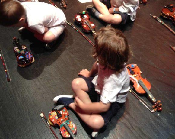 Niñoss sentados en el suelo con violines
