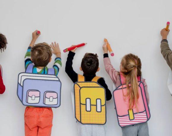 Niños con carteras dibujadas en sus espaldas pintando en la pared