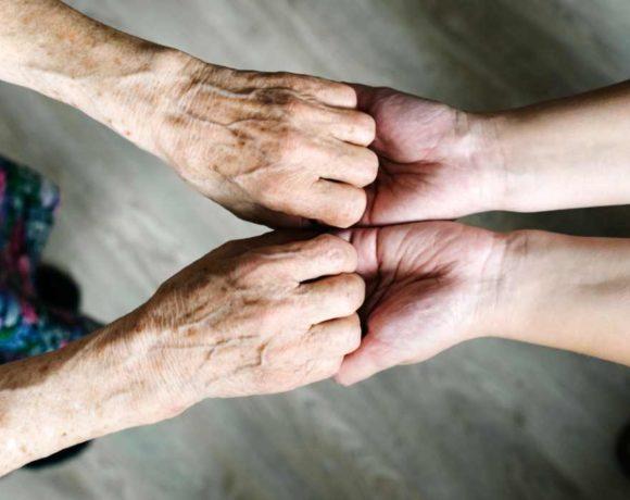 Manos de una persona mayoor sujetadas por otra joven