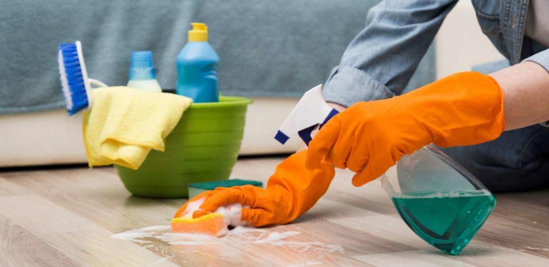 Una persona, provista de guantes, limpiando un suelo