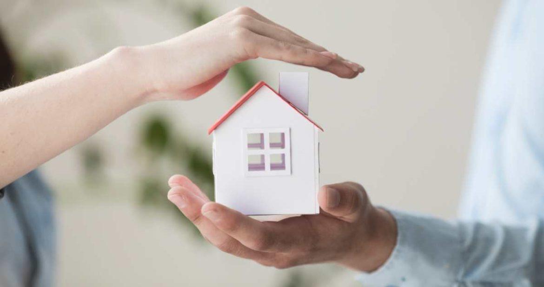 Una manos protegiendo una casa de muñecas