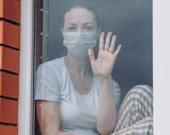 Una mujer con mascarilla en una ventana