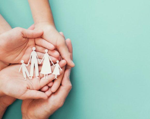 Varias manos sujetan un recortable de una familia
