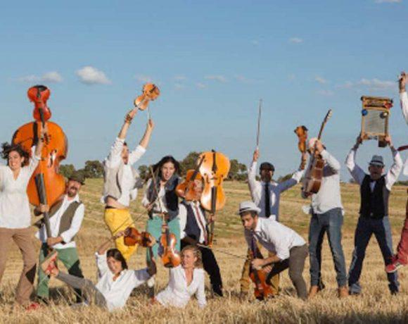 Músicos saltando en el campo con sus instrumentos