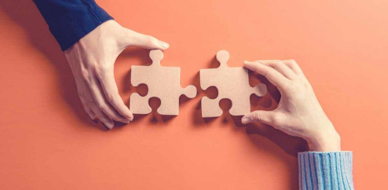 Dos manos sujetan sendas piezas de puzle