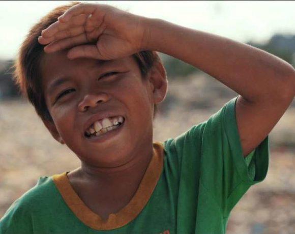 Un niño, con la mano en la frente, sonríe a la cámara