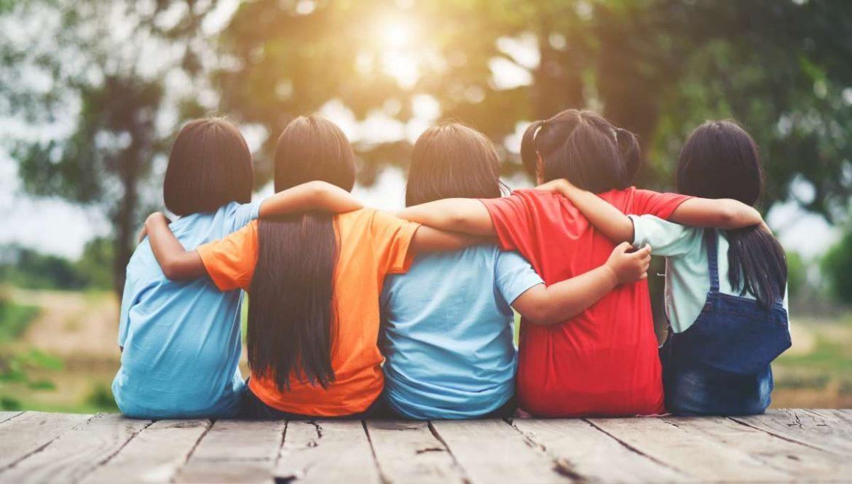 Un grupo de niños sentados de espaldas y abrazados