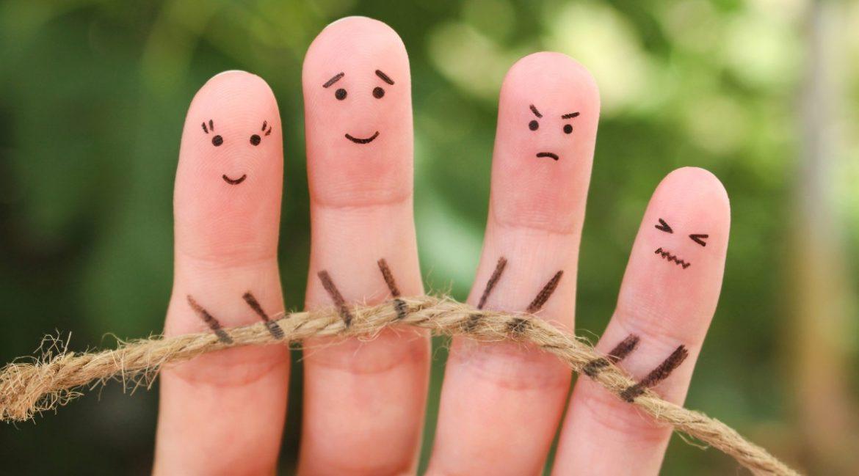 Dedos de una mano con caras con diferentes estados de ánimo